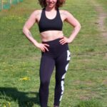 Athletic looking woman, posing with hands on hips, and wearng black leggings and crop top.