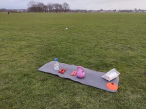 Photo of green space, yoga mat, dumbels and bottle of water at Wanstead Flats | Forest Gate | Leytonstone Personal Trainer