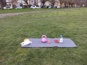 Photo of green space, yoga mat, kettlebell, dumbels and bottle of water at Wanstead Flats | Forest Gate | Leytonstone Personal Trainer